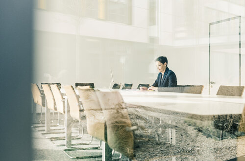 Businesswoman working in conference room - UUF10248