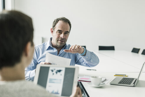 Businessman and businesswoman discussing in conference room - UUF10272