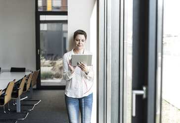 Businesswoman using tablet at the window - UUF10284