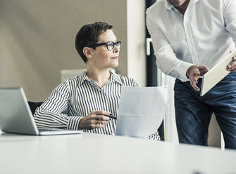 Businesswoman and businessman working in conference room - UUF10290