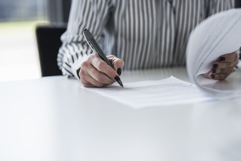 Businesswoman signing document at desk in office - UUF10293