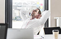 Businessman with earbuds leaning back at desk in office - UUF10296