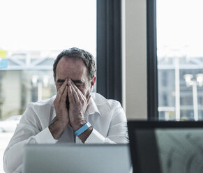 Exhausted businessman sitting at desk in office - UUF10299