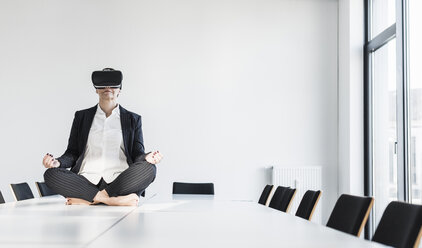 Businesswoman sitting on conference table meditating and wearing VR glasses - UUF10305