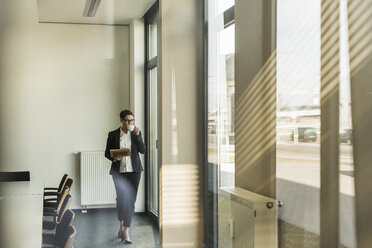 Businesswoman walking in office with coffee and tablet - UUF10308