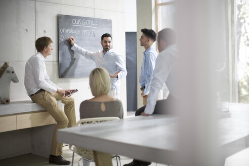 Business people having a business meeting, talking in front of blackboard - ZEF13277
