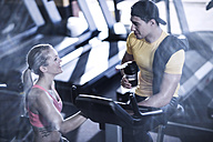 Young man and woman talking in gym - ZEF13324