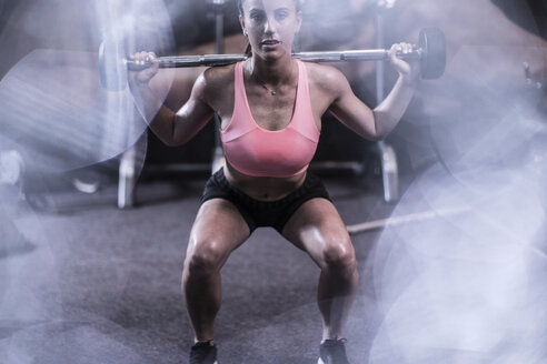 Young woman lifting barbell in gym - ZEF13330
