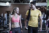 Happy young man and woman talking in gym - ZEF13333