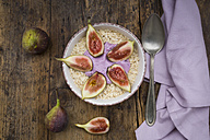 Bowl of overnight oats with blueberry yoghurt and figs on wood - LVF05957