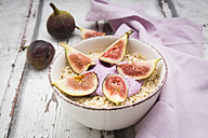 Bowl of overnight oats with blueberry yoghurt and figs on wood - LVF05960