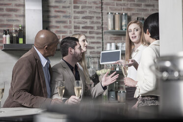 Friends with champagne glasses and tablet at home - ZEF13363