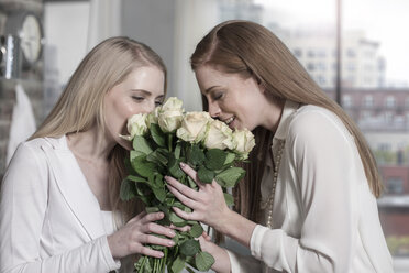 Two young women smelling roses at home - ZEF13366