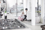 Two women with tablet and magazine in living room - ZEF13369