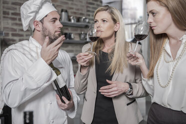 Chef with two women in kitchen tasting wine - ZEF13375
