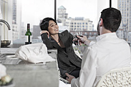 Couple raising a toast in open plan apartment with city view - ZEF13378