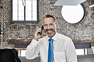 Smiling businessman on cell phone in a loft - FMKF03658