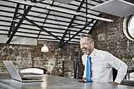 Laughing businessman with laptop sitting at table in a loft - FMKF03661