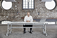 Portrait of confident businessman sitting at rolling table in a loft - FMKF03664