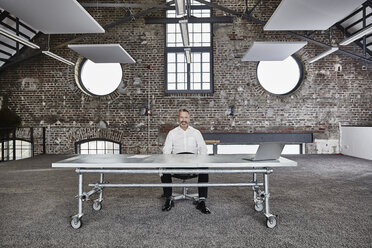 Portrait of confident businessman sitting at rolling table in a loft - FMKF03667