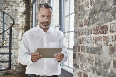 Businessman looking at tablet - FMKF03673