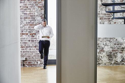 Businessman looking at tablet on modern office floor - FMKF03682