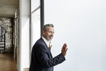 Portrait of confident businessman at the window - FMKF03688