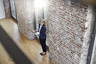 Happy businesswoman on modern office floor using laptop - FMKF03700