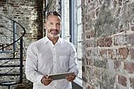 Portrait of confident businessman holding tablet - FMKF03709