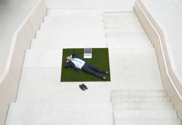 Top view of businesssman lying on stairs next to laptop - FMKF03712
