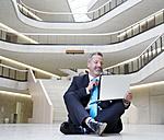 Businesssman sitting on floor in modern office building using laptop - FMKF03715