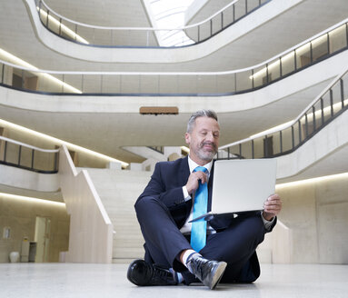 Businesssman sitting on floor in modern office building using laptop - FMKF03715