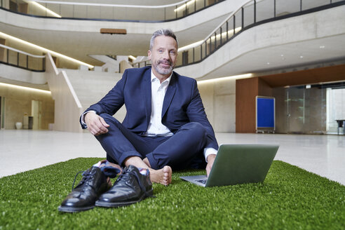 Businesssman sitting on synthetic turf using laptop - FMKF03718