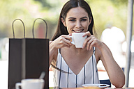 Smiling woman with shopping bag enjoying coffee at cafe - ZEF13393
