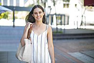 Portrait of smiling young woman in the city - ZEF13396