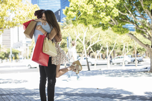 Happy young couple with shopping bags hugging - ZEF13414