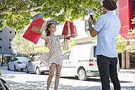 Man taking picture of happy young woman with shopping bags - ZEF13417