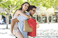 Young man carrying girlfriend with shopping bags piggyback - ZEF13420