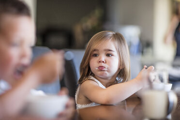 Toddler eating breakfast at table looking at brother - ZEF13431