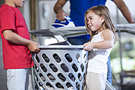 Two children helping father with chores carrying laundry basket - ZEF13440