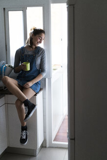 Relaxed young woman at home having a coffee - KKAF00580