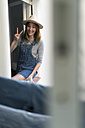 Happy young woman sitting in window frame making victory sign - KKAF00586