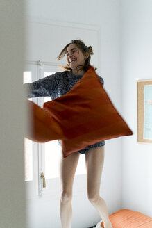 Playful young woman with pillows in bedroom - KKAF00622
