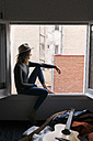 Young woman wearing a hat sitting in window frame - KKAF00631