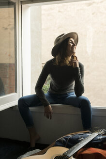 Laughing young woman wearing a hat sitting in window frame - KKAF00634
