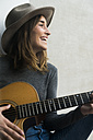 Happy young woman playing guitar - KKAF00637