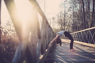 Woman doing wheel pose on a bridge - SIPF01504