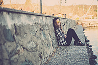 Woman sitting outdoors, leaning on a wall - SIPF01507