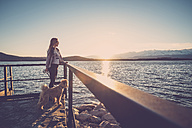 Woman at lake watching sunset with her dog - SIPF01510