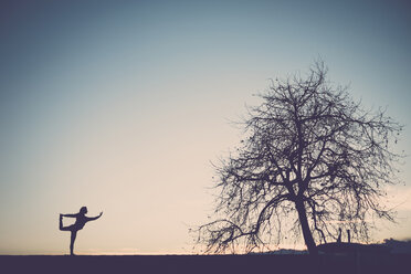 Silhouette of a woman practicing yoga in nature - SIPF01513